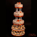 wedding cake with orange and white roses and cupcakes
